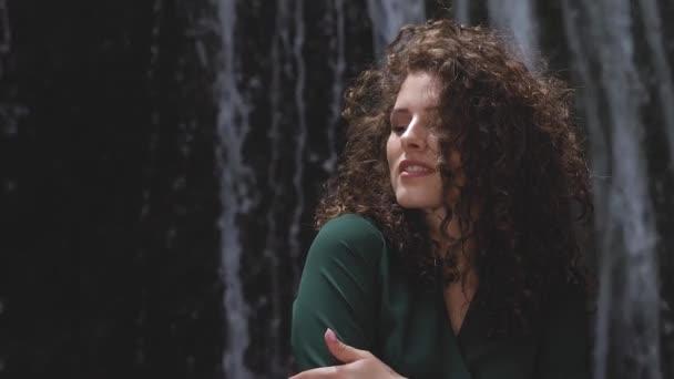 sexy žena se kudrnatými vlasy se uhuje proti vodopádu