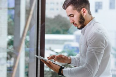 closeup of young arab ethnency man using tablet pc indoor