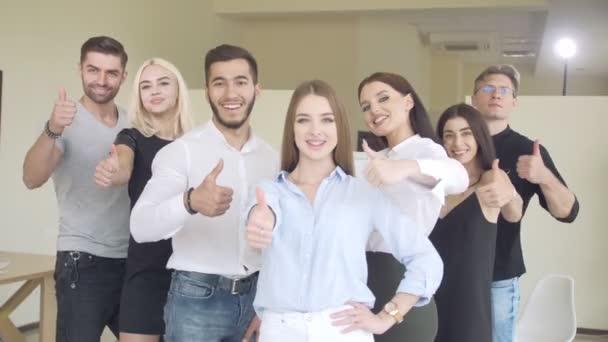 Team junger Leute, die in einem hellen Raum Daumen nach oben drücken