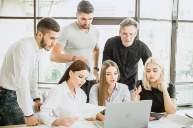 Team of young people in work process in front of laptop