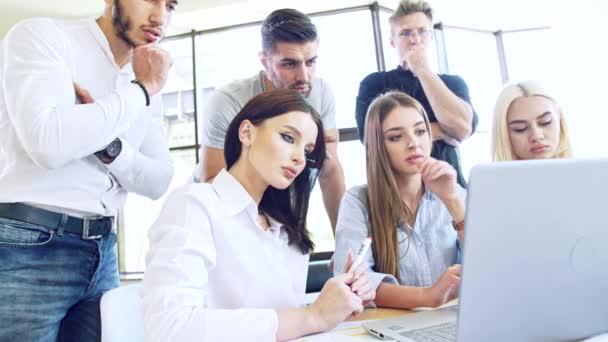 Tým mladých lidí v pracovním procesu před laptopem