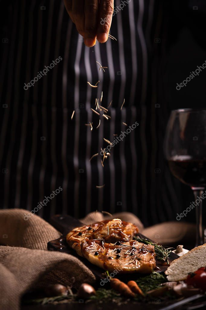 Hand of cook scattering ingredient on beef steak, glass of wine in beside.