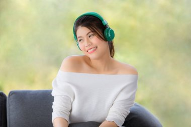 Close up shot portrait of young beautiful Asian woman sitting on sofa  and listening to music with headphone in relaxing manner and hold smarthphone in hand. Green nature blur in background with copy space on the left