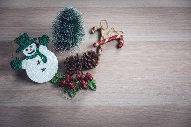 Cute snowman, tiny pine tree, pinecones, glitter holly berries arrange on wood board. Large copy space at right area for wording or pictures.