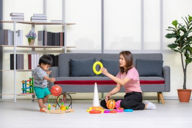 Happy Asian family, young, beautiful mother in pink blouse, sitting on floor, hold yellow ring, adorable little toddler boy in grey T-shirt, short, enjoy playing with ball and toys in cozy living room