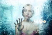 Photo Surreal portrait of young beautiful blonde girl standing behind glass with rain drops touching it with hand. Help concept