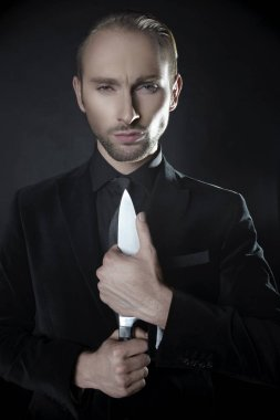 Portrait of businessman in black costume holding knife standing on dark background