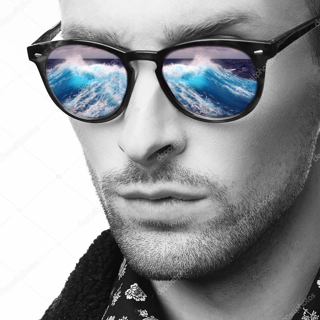 Closeup monochrome portrait of stylish man in sunglasses with reflection of blue ocean waves