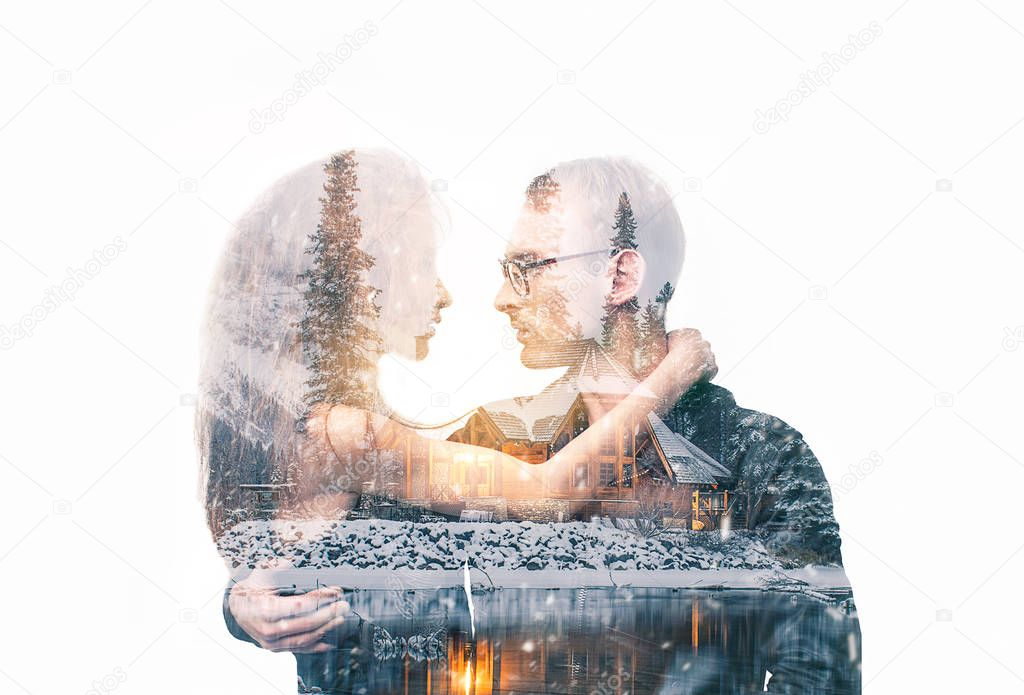 Double exposure portrait of a couple looking at each other with love and embracing. Combined with photograph of wooden country house and snow background. People, christmas, holidays and season concept