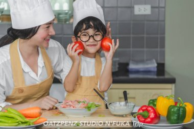 Asian woman young mother with son boy cooking salad food  with v
