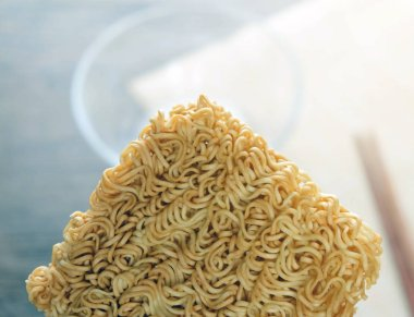 Close up of instant noodle with glass bowl and chopsticks backgroun