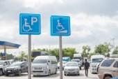Fotografie Behindertenparkschild an Tankstelle.