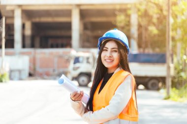Asian woman architect wearing blue safety helmet checking working progress at construction site.
