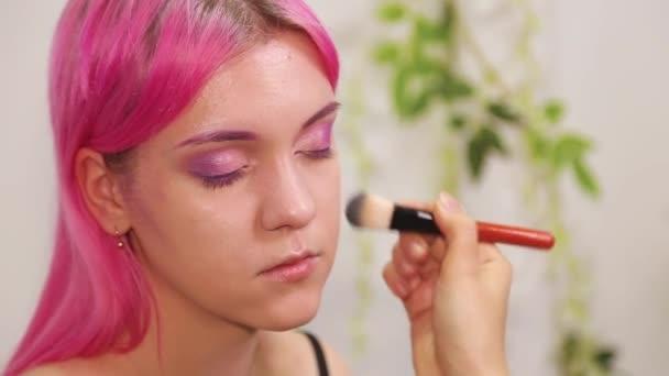 Közelkép egy lány arcáról az alapozás folyamatában a bőrön. Sminkes művész a munkafolyamatban csinál smink egy lány.