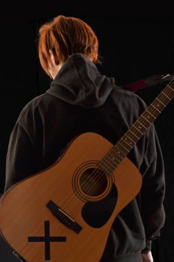 Musician singer artist holding a guitar on black background.