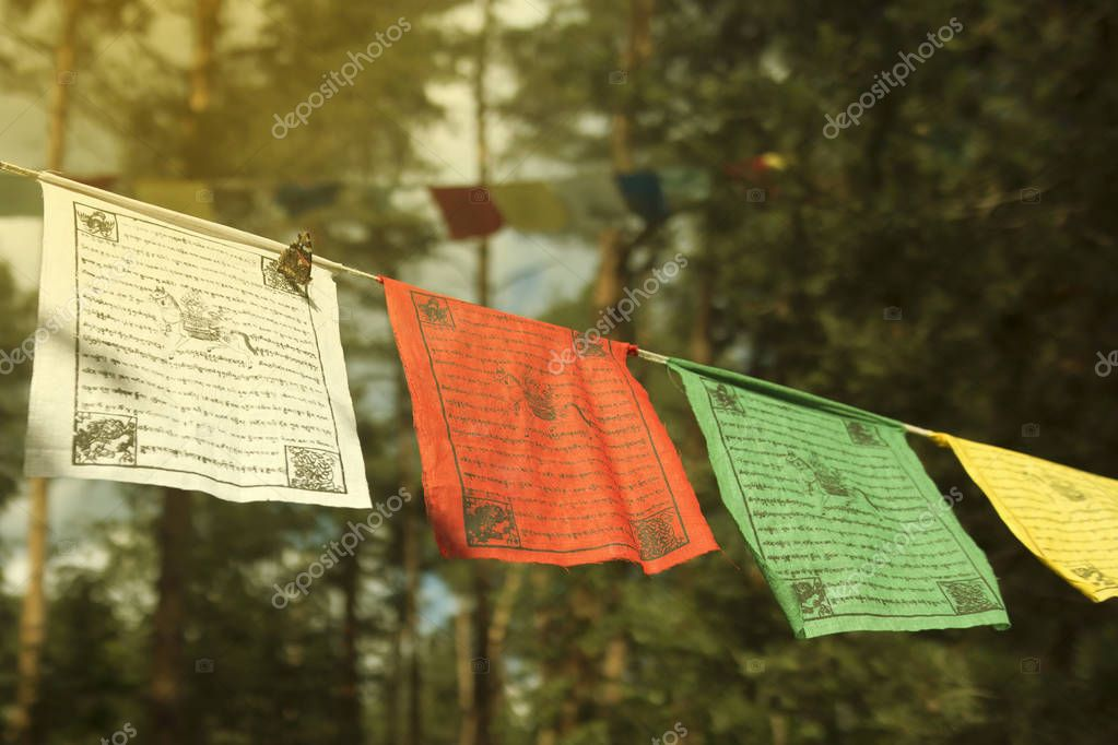 Colorful prayer flags (lungta/darcho) of Buddhist philosophy with blurry text in the wind. The red admiral butterfly (Vanessa atalanta) sits on a white flag. Soft focus with bokeh
