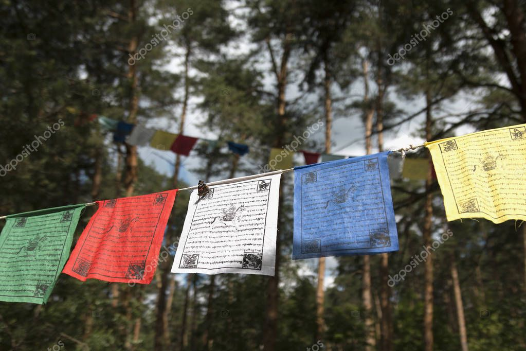 Kunsangar north, Pavlovsky Posad, Moscow region / Russia - July 2017: Colorful prayer flags (lungta/darcho) of Buddhist philosophy on the forest background. Soft focus with bokeh