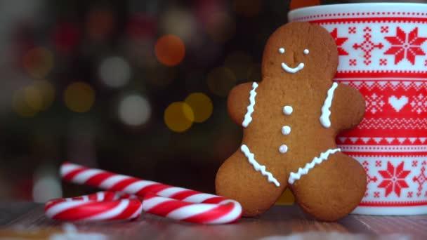 Karácsonyi videó mézeskalács ember piros bögre karácsonyi dísz könnyű bokeh a karácsonyfa és piros csíkos ünnepi cukorkák. Karácsonyi cukorka és csésze mályvacukor fa háttér. 4k videó