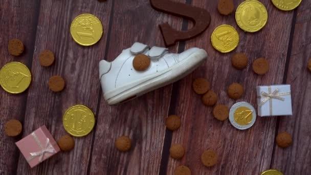 Holländischer Feiertag Sinterklaas Hintergrund. Rotation Kinderschuh, Karotten für das Pferd des Weihnachtsmannes, Geschenke, traditionelle Süßigkeiten pepernoten und Schokoladenbrief. Schötje zetten. 4k-Video