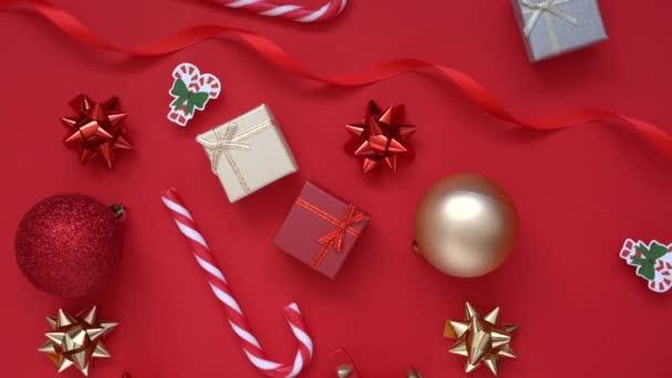 Vánoční pozadí. Rotace 4k Video s dárkové dárkové dárkové krabice, jedle větve stromů a mnoho vánoční pruhované bonbóny, červené slavnostní dekorace na červeném pozadí. Vánoční a novoroční prázdninový koncept