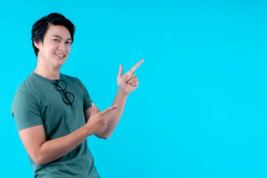 hand gesture present and hand finger point of handsome attractive asian male shake move body hand gesture with fun and happiness big smile casual costume blue background