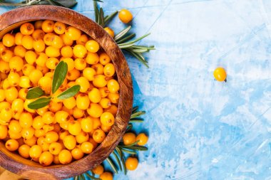 Sea buckthorn berries in wooden bowl on blue background