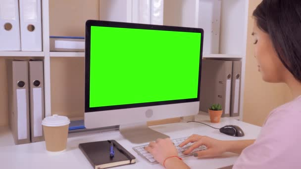 side view business woman sitting at the desk in front of computer monitor with isolated green screen female entering data on white keyboard moving pc mouse