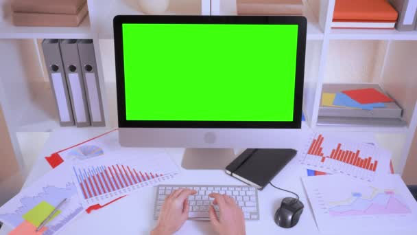 top view unrecognizable business person working on computer. manager hands typing on white keyboard. workplace with white desk folders financial schedule and charts using pc mouse display with isolated green screen