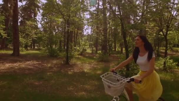 Kavkazský žena s dlouhé červené vlasy si aktivní životní styl. Žena, jízda na kole v parku se zelenými borovicemi letní sezóny světla slunce