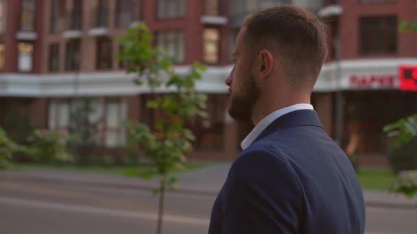 side view of fair haired man walking along sidewalk