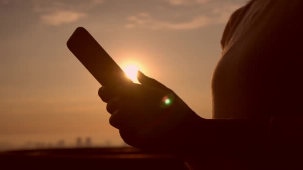 faceless person using smartphone against sunset background