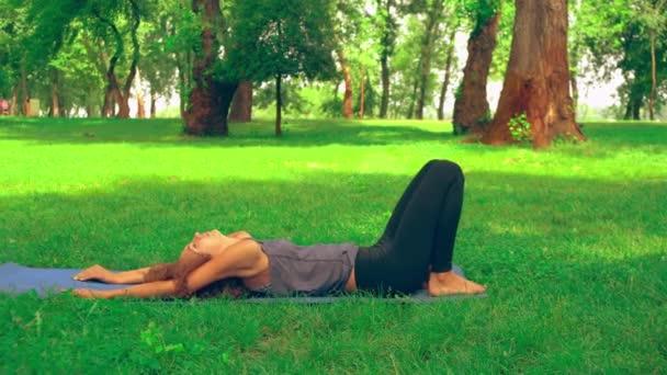 štíhlá žena cvičení asana v parku leží na modrém mat. kavkazský dívky s dlouhými kudrnatými vlasy vlaky venku. přírodní krajina s trávou a stromy