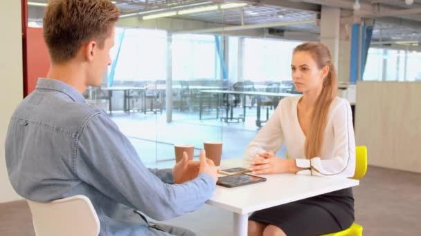 Dva mladí obchodní kolegové s přestávce na kávu