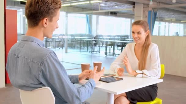 Two cheerful colleagues discussing in modern office