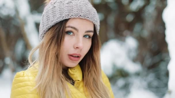 Charming woman with blue eyes stands in winter hat in the forest covered with snow. Portrait of smiling girl enjoying wintertime. Shot on Red Epic