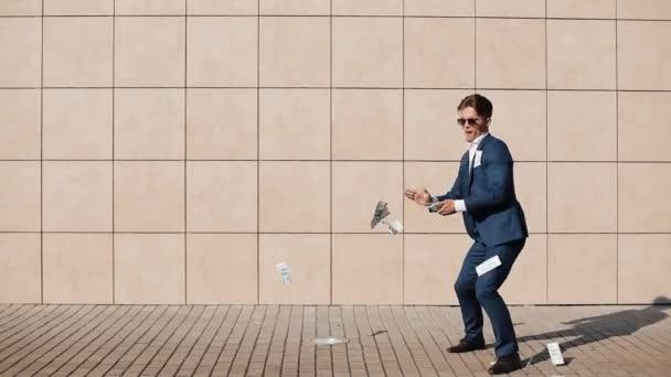 Mladý šťastný podnikatel bodový dolary a tančí na ulici. Nachází se poblíž centra office, zpomalené. Úspěšné podnikání