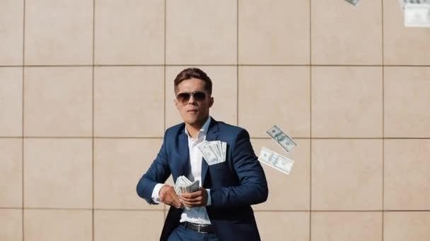 Mladý šťastný podnikatel bodový dolarů a zábavné tance na ulici. Chůze nedaleko centra office, zpomalené. Peníze déšť, úspěšné podnikání