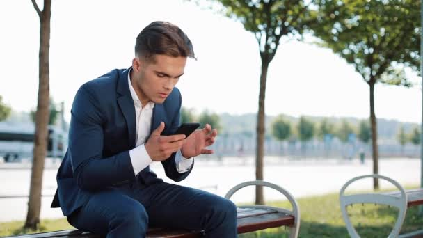 Unhappy businessman with smartphone reading bad news in on the bench on the street. Upset sales agent stock exchange bad news smartphone call problem finance crisis