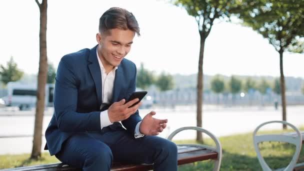 Glückliche junge Geschäftsmann Jubel feiert Smartphone betrachten. Gute Nachrichten in Unternehmen. Leistung und Erfolg, Gewinn, Sportwetten, Smartphone-app-Konzept