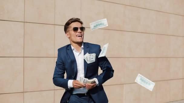 Mladý podnikatel šťastný tanec a házet peníze. Zpomalený pohyb. Úspěšné podnikání nebo výhra v loterii