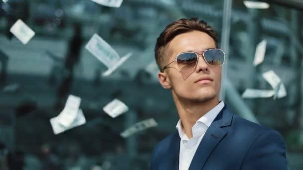 Klesající dolarů na mladých šťastný podnikatel. Peníze déšť. Koncept podnikání, lidé a finance