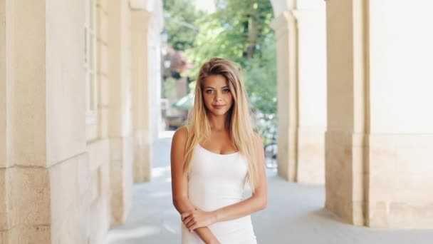 Egy szép fehér ruhában, fordult a kamera, és mosolyog, állandó cam lövés, lassú mozgás-vonzó fiatal nő portréja