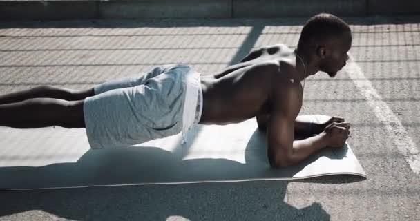Sportovní afroamerické muže vykonávající prkno na ulici školení. Mladý muž cvičení ve sportovní chlap cvičení poblíž sportovního stadionu. Cross fit trénink. Svalnatý černoch tlačí venkovní