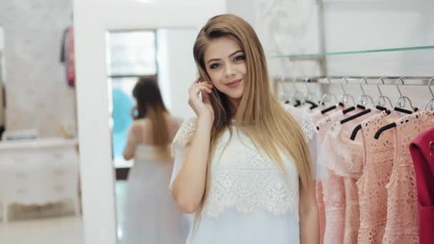 Beautiful shopping woman in the dressing room, poses on the camera in a new dress. Young attractive girl in a dressing room at a shopping center Clothing, fashion, wardrobe, style and people concept