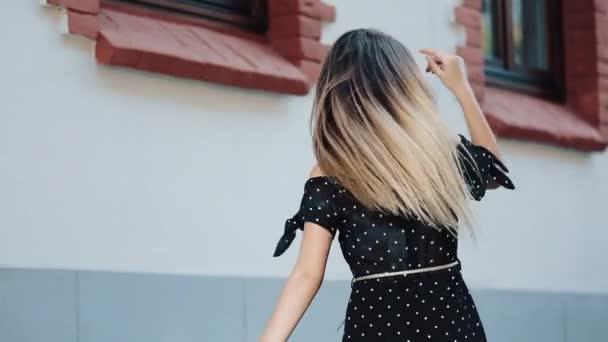 junge verführerische Frau im sexy schwarzen Kleid, die durch die Straßen der alten europäischen Stadt spaziert. natürliche Schönheit, weibliches Porträt, verführerischer Blick. Selbstbewusstes Konzept