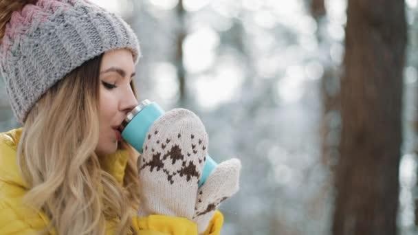 Hezká žena v zimní čepice má sníh a pití horké nápoje, stáli venku na sněhu v lese. Dívka si zimu venku. Vánoční svátky