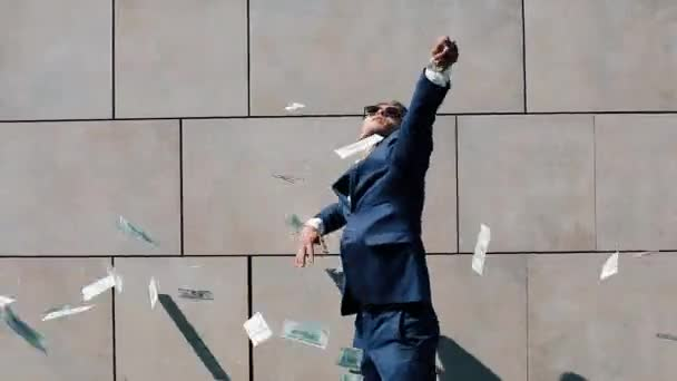 Mladý šťastný podnikatel bodový dolarů a zábavné tance na ulici. Peníze déšť, padající dolarů. Nachází se poblíž centra office, zpomalené. Úspěšné podnikání. Střílel na Red Epic
