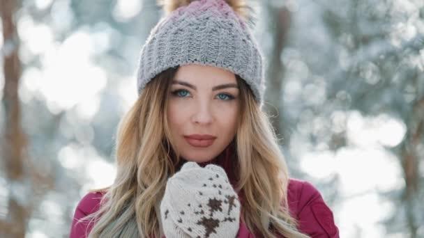 Hezká žena v zimní čepice úsměvy stáli venku na sněhu v lese. Portrét krásné dívky při pohledu do kamery. Zimní čas odpočinku, Zimní prázdniny, Vánoce, dovolená