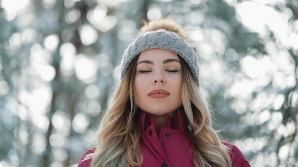 Pretty woman in winter hat enjoys the snow standing outside on the snow in the forest. Winter mountain forest resting walks