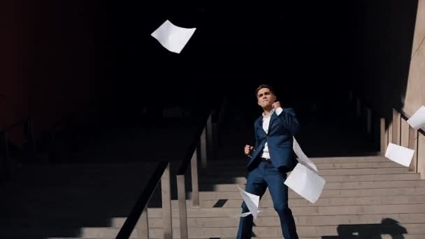 Young businessman throwing document and funny dancing near office building. Successful lifestyle, contract, responsibility. Business, people, paperwork conception